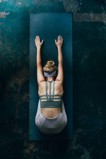 selbstfürsorge rituale: blonde frau macht yoga zu hause, ein overhead-blick - aktiver lebensstil stock-fotos und bilder