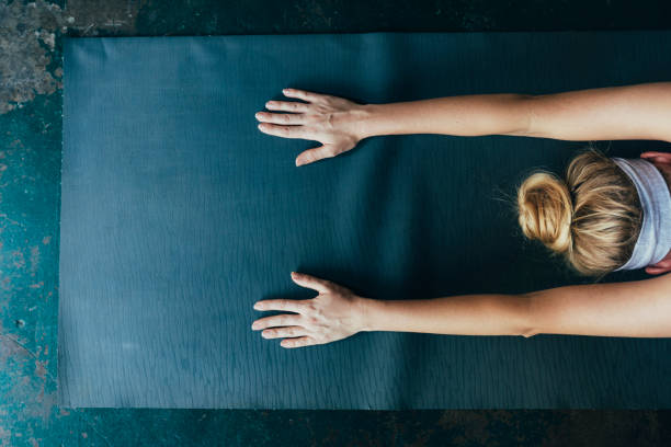 Self Care Rituals: Unrecognizable Blonde Woman Doing Yoga at Home Blonde woman relaxing at home in the Child's yoga pose, a close up. childs pose stock pictures, royalty-free photos & images