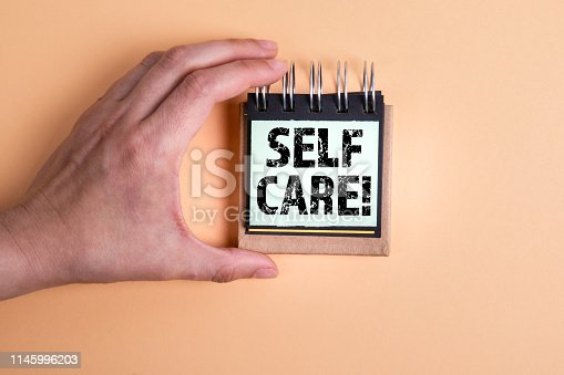 1175869940 istock photo Self Care. Woman's hand and note pad 1145996203