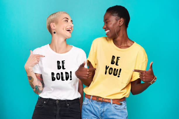 Self confidence is the biggest fashion statement Studio shot of two confident young women pointing at their statement t shirts against a turquoise background girl power stock pictures, royalty-free photos & images