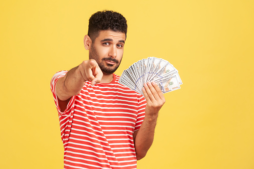 Self confident rich man with beard in striped t-shirt holding fan of dollars and pointing finger at camera with serious expression, easy profit. Indoor studio shot isolated on yellow background