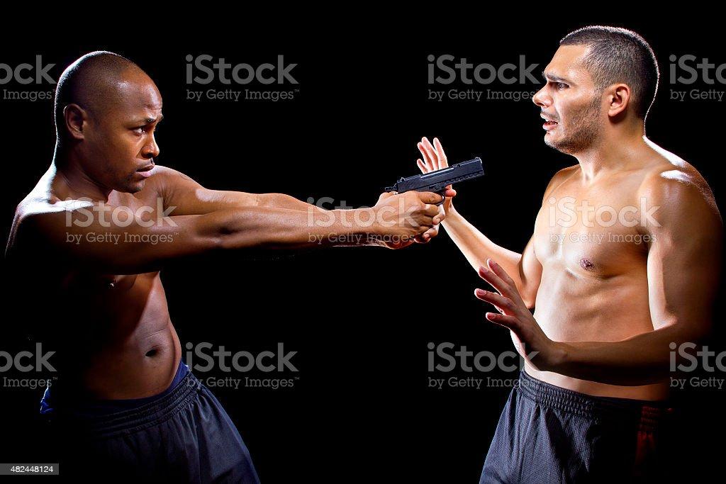 Photo of a martial artist disarming a criminal with a gun or...