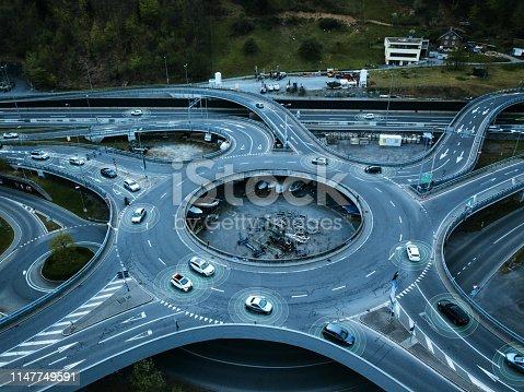 936364312 istock photo Self Driving Autonomous Cars on Traffic Circle 1147749591