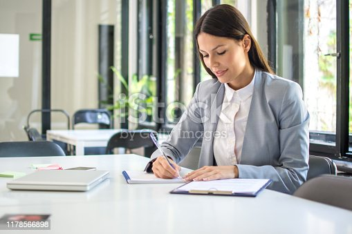 Self employed female entrepreneur taking notes while working with papers in office
