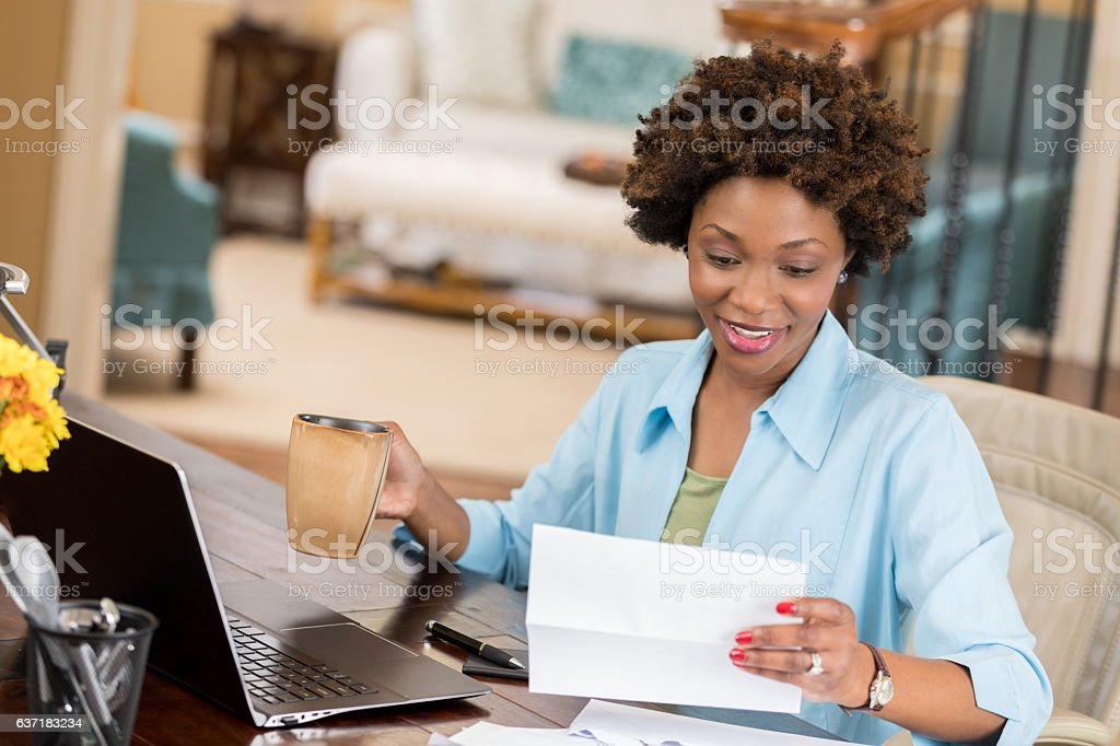 Self employed woman reads her mail in home office stock photo