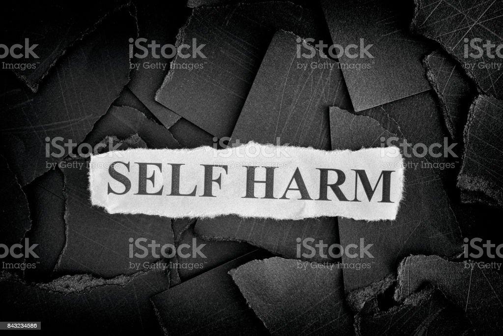 L'automutilation. Morceaux déchirés de papier noir et mots Self Harm - Photo