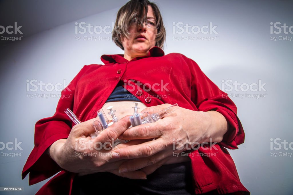Adult woman holding syringes from diabetic therapy with bruises on...