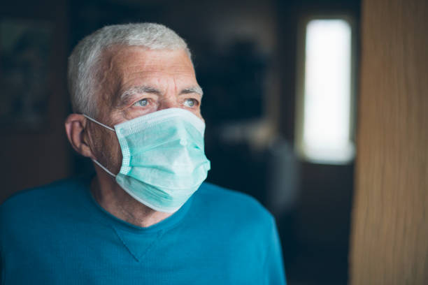 Self isolation an protection for senior citizens Senior man wearing a protective mask at home, during COVID-19 pandemic. flatten the curve stock pictures, royalty-free photos & images
