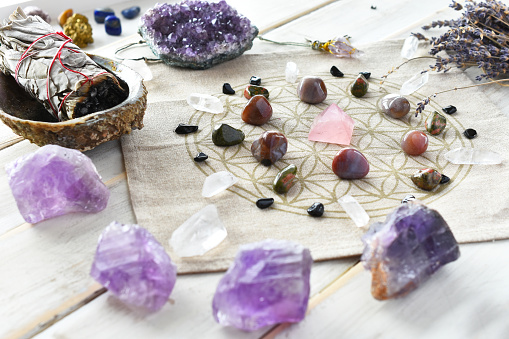 A close up image of a self love crystal grid using the flower of life sacred geometry grid cloth and amethyst crystals.