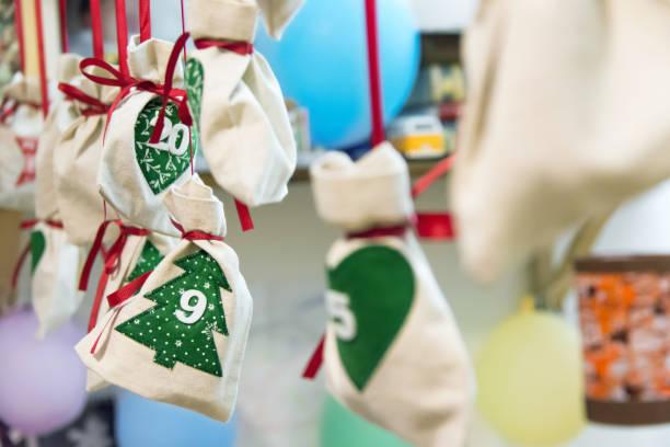 Selbst gemacht Adventskalender Leinen Taschen Säcke mit Weihnachtsbaum Ornament mit Datteln gebunden mit roten Seidenband hängen auf Schnur in Kinderzimmer gebunden. Feiertagsvorbereitungsfeier – Foto