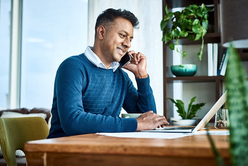 Shot of a businessman using a laptop and smartphone while working from home