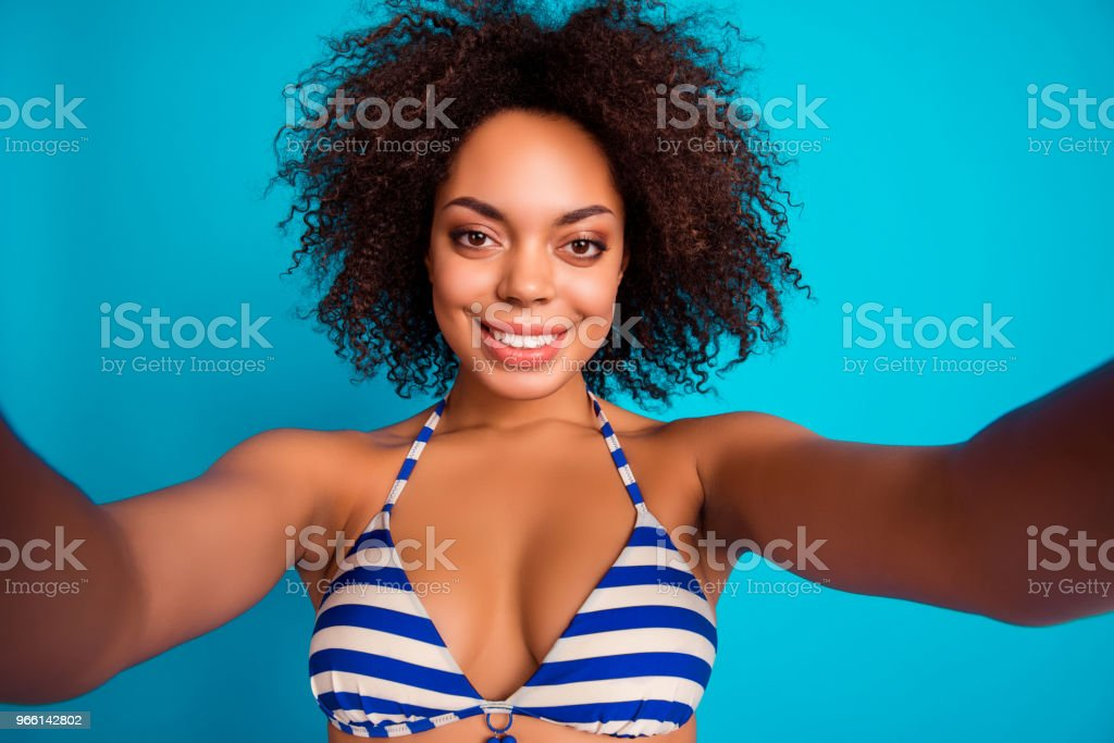 Self photo, portrait of cute lovely nice-looking fresh sexy afro woman with soft fluffy  voluminous curly brown hair, she has video conversation via internet, isolated on blue background - Стоковые фото Африканская этническая группа роялти-фри