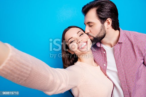 istock Self portrait of attractive lovely couple, man with stubble kissing in cheek lover shooting selfie on front camera, celebrating 14-february, isolated on bright blue background 968819710