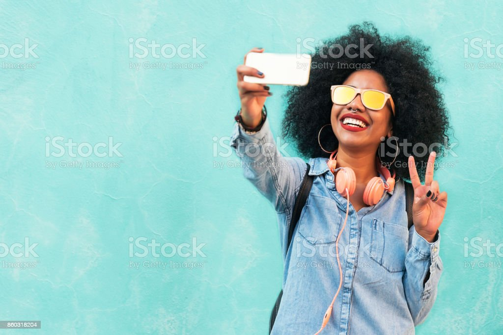 Self portrait of beautiful young afro american woman making peace sign. stock photo