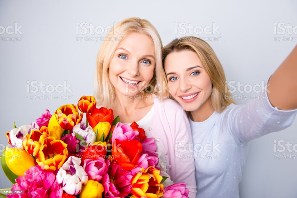 Self portrait of cheerful creative positive blogger shooting selfie on front camera with her grandmother having big colorful bouquet of tulips hugging bonding isolated on grey background royalty-free stock photo