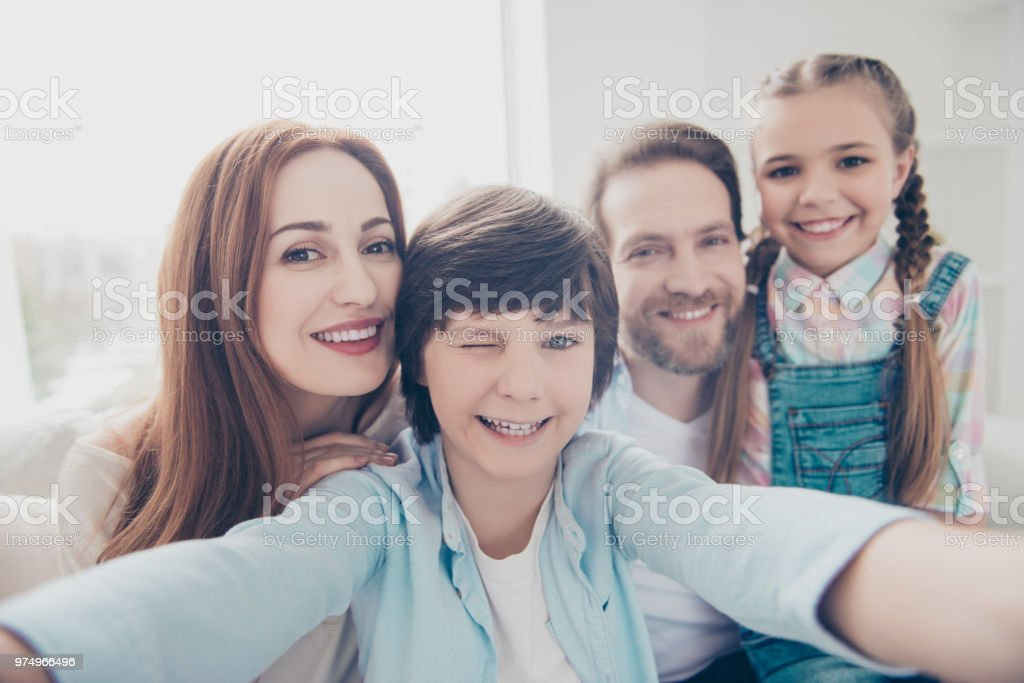 Self portrait of cheerful joyful four people shooting selfie on front...