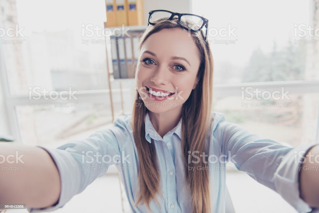 Self portrait of cheerful, positive, charming woman with hairstyle and glasses on head shooting selfie with two arms on front camera of smart phone in work place, station royalty-free stock photo