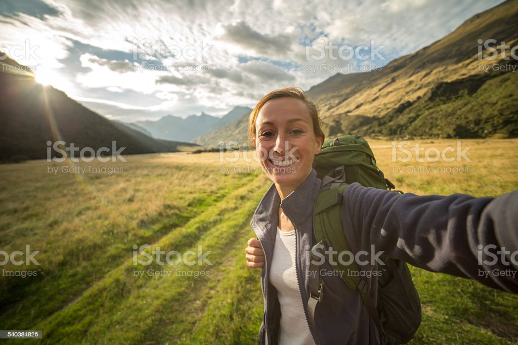 Self portrait of female hiking in the valley at sunrise stock photo