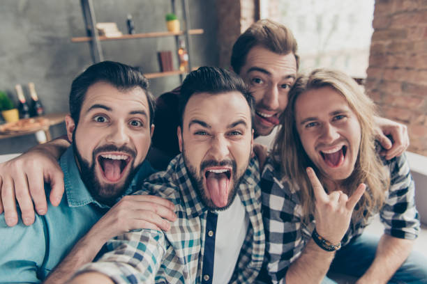 Self portrait of four attractive comic crazy funny foolish guys with hairstyle, showing tongue out and rock and roll symbol, making selfie on smart phone, front camera, sitting on couch in livingroom Self portrait of four attractive comic crazy funny foolish guys with hairstyle, showing tongue out and rock and roll symbol, making selfie on smart phone, front camera, sitting on couch in livingroom bachelor stock pictures, royalty-free photos & images