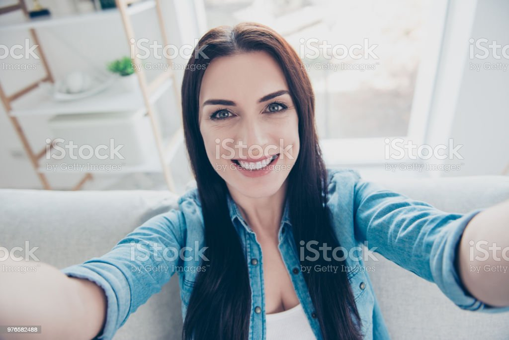 Self portrait of gorgeous sensual woman with white smile shooting selfie with two hands on front camera sitting in apartment indoor stock photo