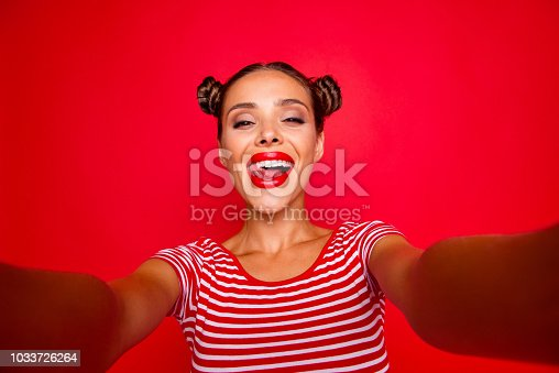 Self portrait of happy pretty positive girl shooting selfie on front camera with two hands having video-call with friend isolated on red background. Joy fun concept