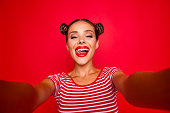 istock Self portrait of happy pretty positive girl shooting selfie on front camera with two hands having video-call with friend isolated on red background. Joy fun concept 1033726264