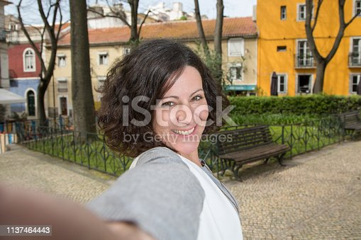 istock Self portrait of joyful tourist in old district alley 1137464443