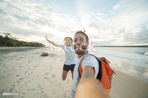 Cheerful young couple on the beach take a selfie portrait at sunset. The female is jumping on the background.