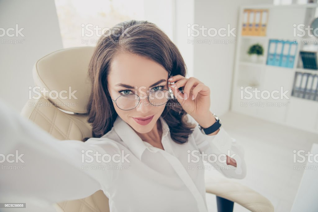 Self portrait of pretty, charming, joyful, positive, cheerful, trendy, stylish, brunette woman with hairdo shooting selfie on front camera holding eyelet of glasses on her face with hand - Foto stock royalty-free di Abbigliamento