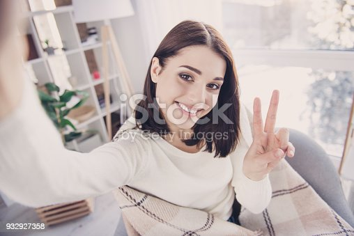 istock Self portrait of pretty, charming, nice, cute, stylish, brunette girl in pullover with modern hairstyle, shooting selfie gesturing v-sign to the front camera, wrapped in plaid, sitting in living room 932927358