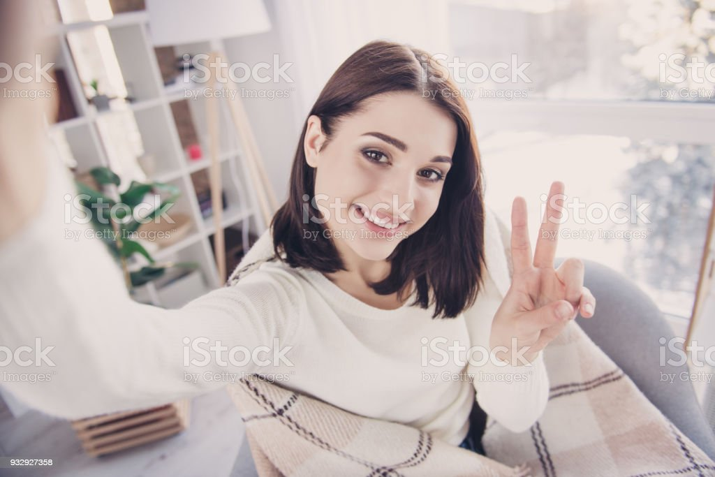 Self portrait of pretty, charming, nice, cute, stylish, brunette girl in pullover with modern hairstyle, shooting selfie gesturing v-sign to the front camera, wrapped in plaid, sitting in living room stock photo