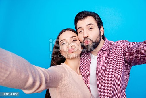 490225014istockphoto Self portrait of trendy lovely couple shooting selfie on front camera sending kisses with pout lips isolated on blue background. Rest relax valentine day concept 968820088