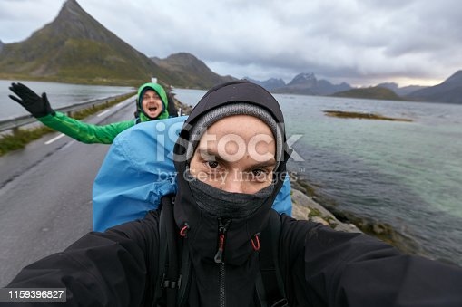 They are wearing warm outdoor clothes and backpacks.  Their faces are covered with a hood. Image taken on the way to Fredvang.