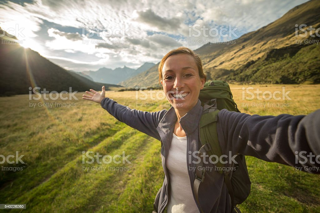 Self portrait of woman hiking in the valley at sunrise stock photo