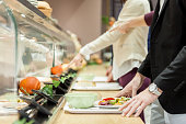 Business people waiting in line in self service restaurant, seafood on plate