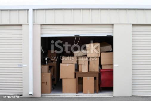 Warehouse building with self storage units. Self storage facility. Roll up doors on self storage facility. One door open with boxes and furniture in doorway.