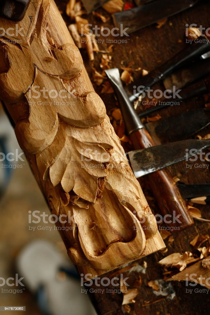 self taught skilled Thai man carving an intricate decoration on a hardwood table leg in his workshop using hand tools, Southeast Asia stock photo