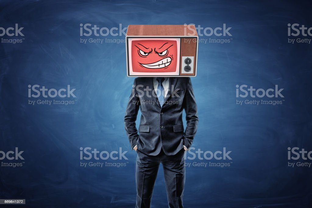 A self-assured businessman holds his hands in pockets and wears an old TV with an angry smiley face on his head. stock photo
