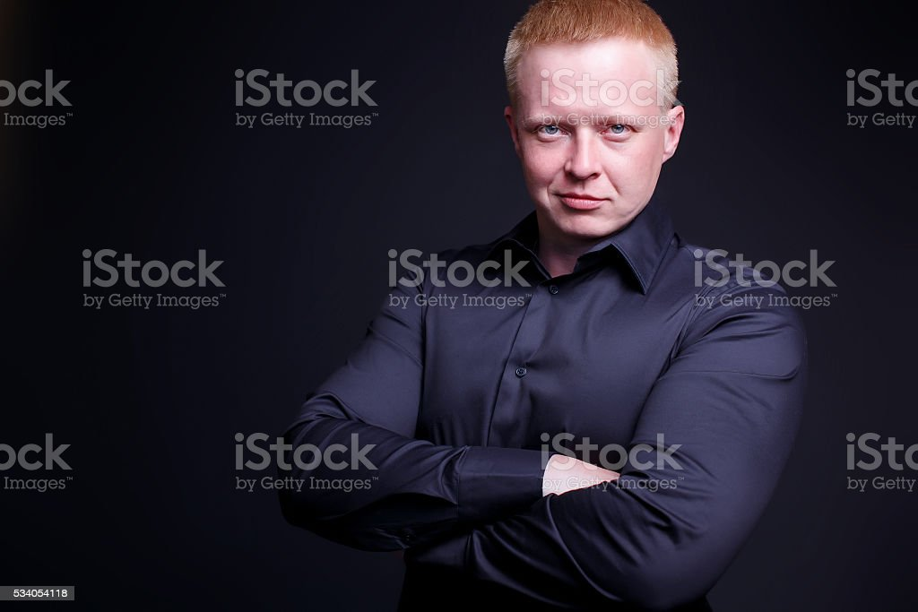 self-confident man smiling with his arms crossed stock photo