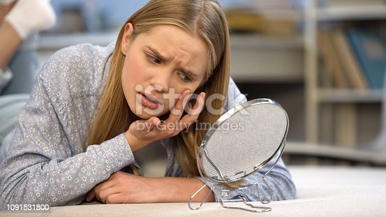 istock Self-criticism, upset teenage girl looking at her problematic skin condition 1091531800