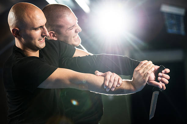 Self-defending from attacker with a knife. Mid adult martial artist self-defending from an attacker who is holding a knife.   self defense stock pictures, royalty-free photos & images