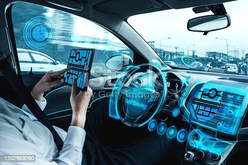 692832436 istock photo Self-drive autonomous car with man at driver seat. 1202869260