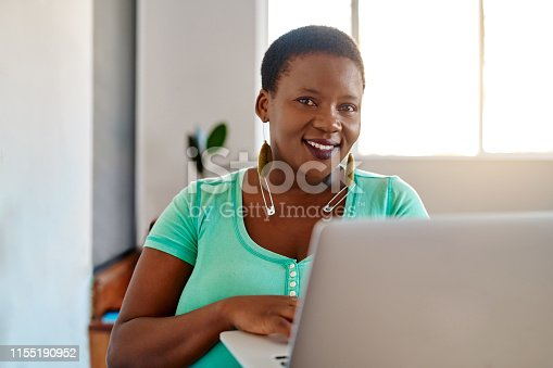 Portrait of a young woman using a laptop while working from home