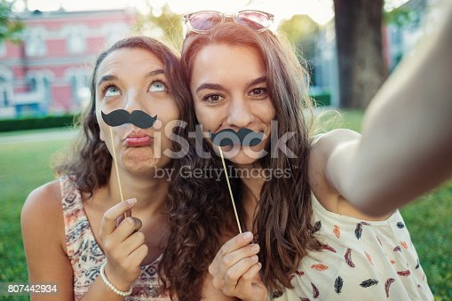 Two pretty girls making selfie with fake paper mustaches