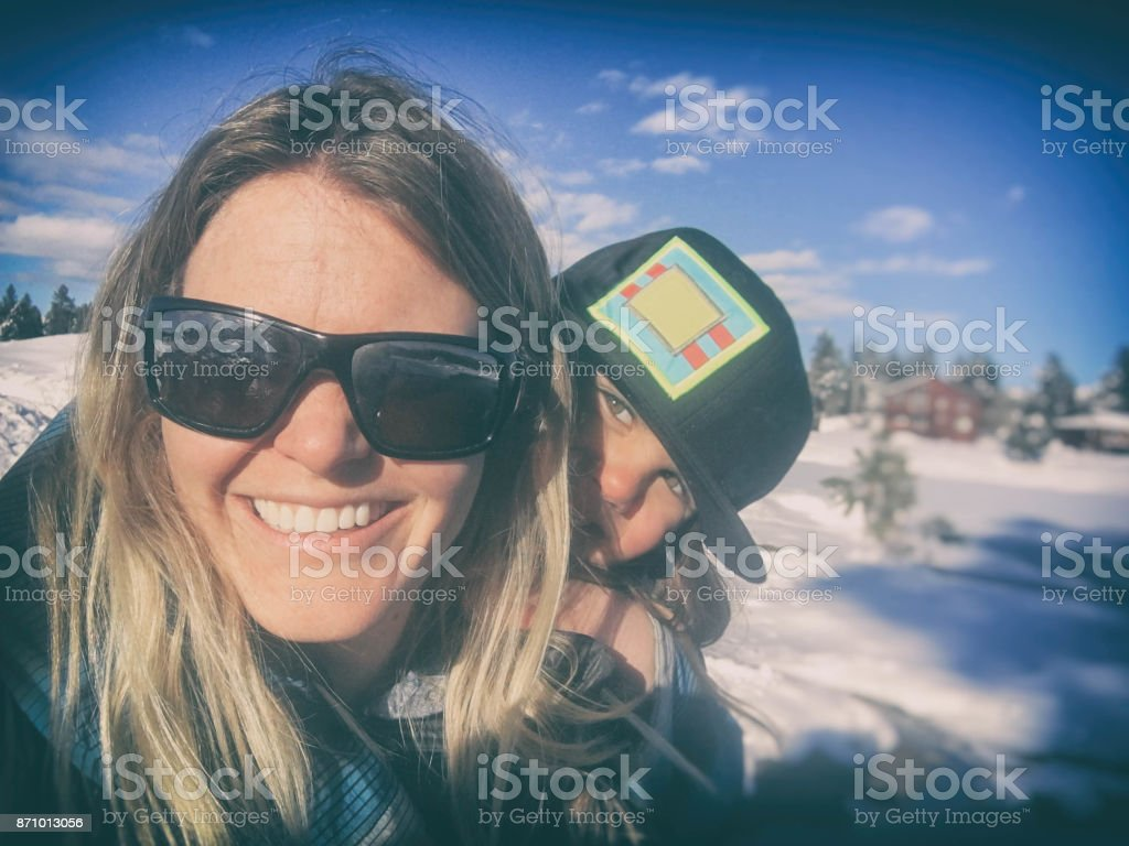 Selfie and piggybacks in the snow stock photo