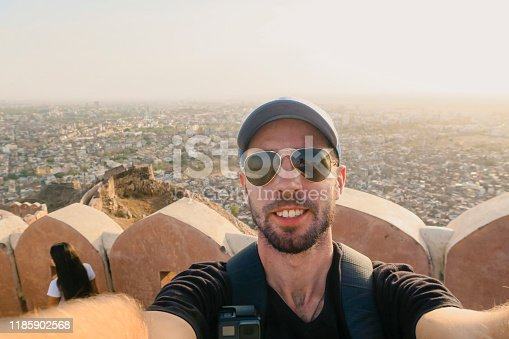 A selfie shot of a male tourist from the stone railing on the roof terrace of Nahargarh Fort in Jaipur, Rajasthan, India. Nahargarh means