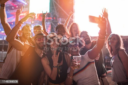 Multi ethnic group of friends having good time at summer festival, they drinking beer, enjoy in music and take selfie. Summer sunset. They ware casual clothing
