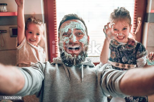 istock Selfie By Father With Cute Child Daughters After Cooking And Making Mess With Topping 1302800109