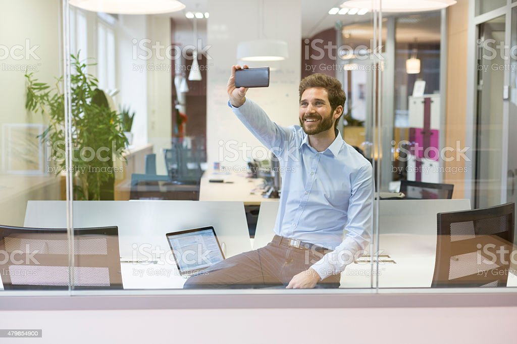 Selfie casual businessman taking pictures in open space office stock photo