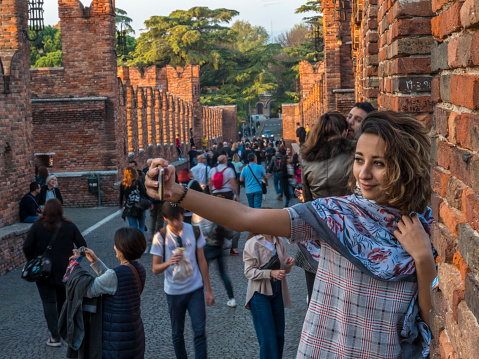 Dozens of tourists visit and take photos and selfies on the  Castel vecchio bridge, one of the symbols of Verona, Italy